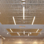 Установленные встроенные светильники на деревянном декоративном реечном потолке.