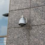 Установленная уличная купольная видеокамера на фасаде здания.