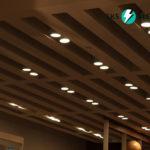 Установленные встроенные светильники на деревянном декоративном реечном потолке